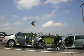 Two vehicles crashed apparently head-on Friday. In the photo, one of the four helicopters departs with an injured victim. Copyright 2015, River Raisin Publications, Inc.