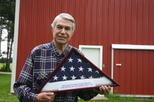 """World War II orphan Ferenz """"Fritz"""" Whitman of Riga displays the flag he received when he became a U.S. citizen."""